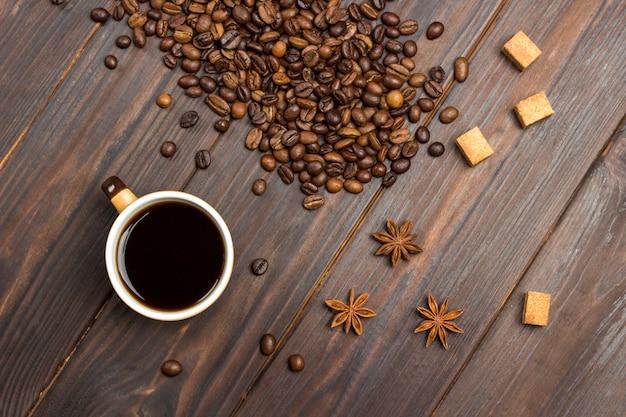 Tasse kaffee. auf dem tisch verstreute kaffeebohnen, sternanis und braune zuckerstücke.