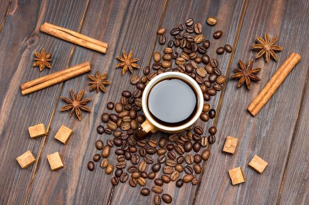 Tasse kaffee. auf dem tisch verstreute kaffeebohnen, sternanis, zimtstangen und braune zuckerstücke.