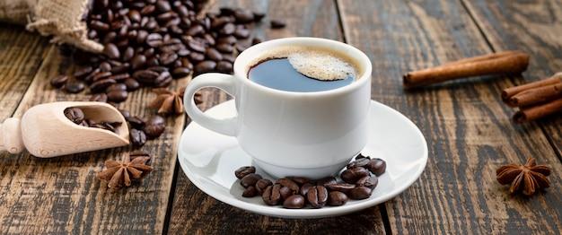 Tasse kaffee auf einem holztisch. das konzept der herstellung von natürlichem kaffee aus hochwertigen kaffeebohnen. banner