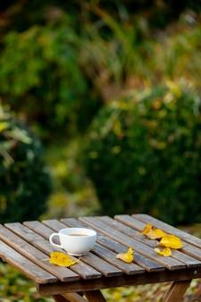 Tasse kaffee auf einem holztisch in einem garten