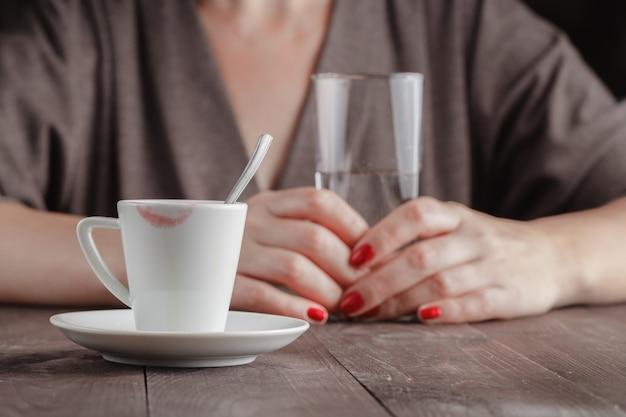 Tasse kaffee auf einem holztisch mit glas wasser in frauenhänden