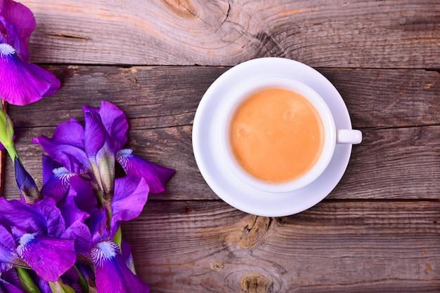 Tasse kaffee auf einer untertasse neben einem strauß lila iris
