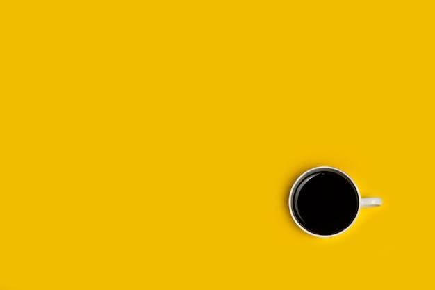 Tasse kaffee auf gelbem hintergrund in einer draufsicht
