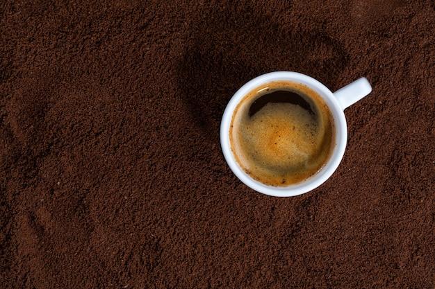 Tasse kaffee auf gemahlenem kaffee. nahansicht.