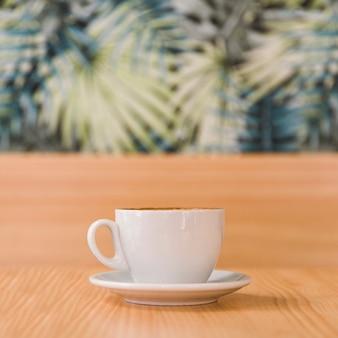 Tasse kaffee auf hölzernem schreibtisch