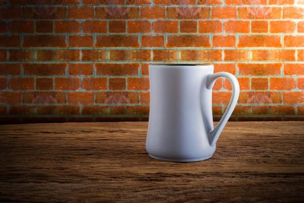 Tasse kaffee auf hölzerner tischplatte gegen schmutzwand