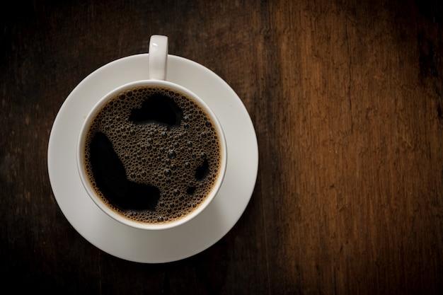 Tasse kaffee auf holztisch. speicherplatz kopieren. draufsicht. flach liegen