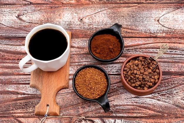 Tasse kaffee auf kleinen kaffeebohnen des hölzernen brettes auf holzoberfläche