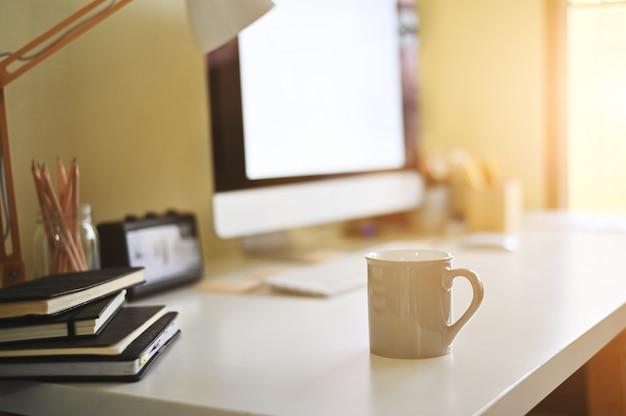 Tasse kaffee auf kreativem schreibtisch.