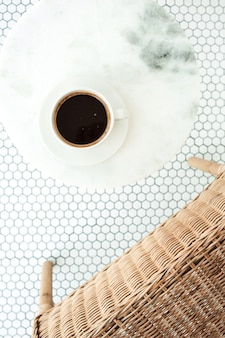 Tasse kaffee auf marmor-couchtisch auf weißer mosaikfliese mit rattanstuhl