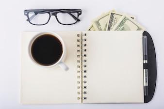 Tasse Kaffee auf Notizbuch mit Gläsern auf Schreibtisch