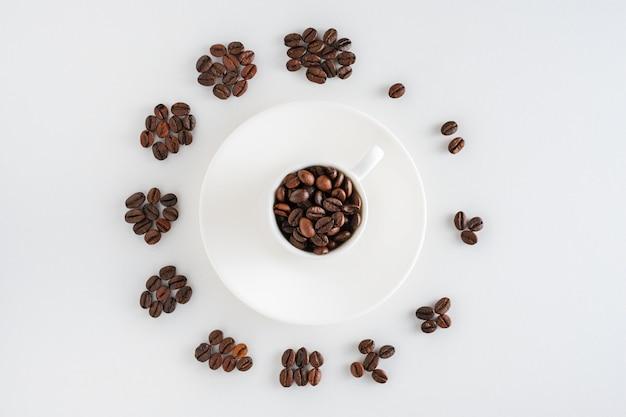 Tasse kaffee auf saucer und kaffeebohnen in form einer uhr