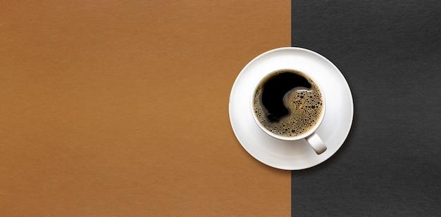 Tasse kaffee auf schwarzem und braunem papier