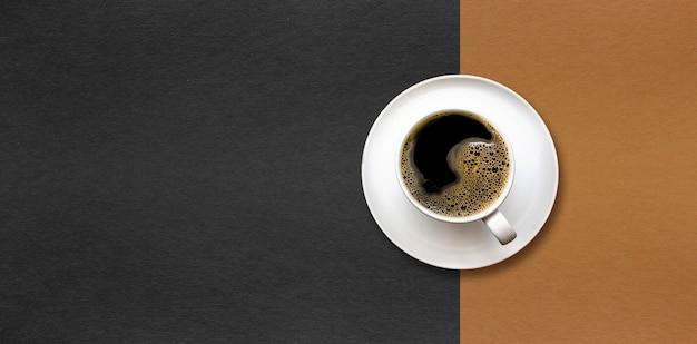 Tasse kaffee auf schwarzem und braunem papierhintergrund.