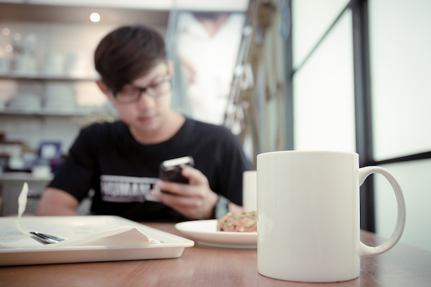 Tasse kaffee auf tabelle im café mit unscharfem fokus ein mann las e-mails im smartphone.