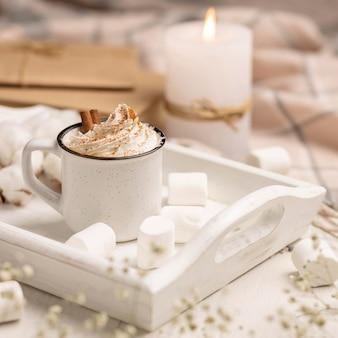 Tasse kaffee auf tablett mit schlagsahne und kerze