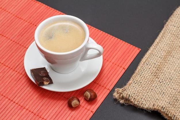 Tasse kaffee auf untertasse mit stück schokoriegel, nüssen auf bambusserviette und sackleinentasche auf schwarzem hintergrund. ansicht von oben.