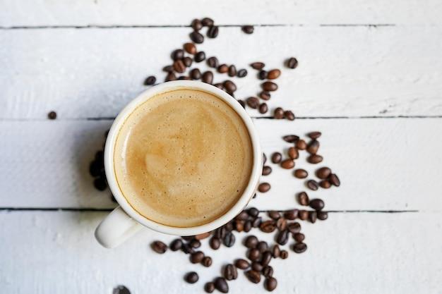 Tasse kaffee auf weißem hölzernem mit kaffeebohnen