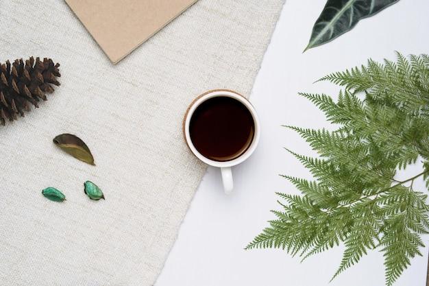 Tasse kaffee auf weißem hölzernem und braunem garnhintergrund