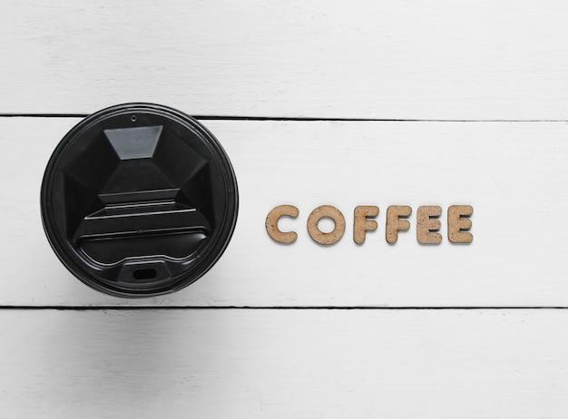 Tasse kaffee auf weißem holz mit dem wort kaffee