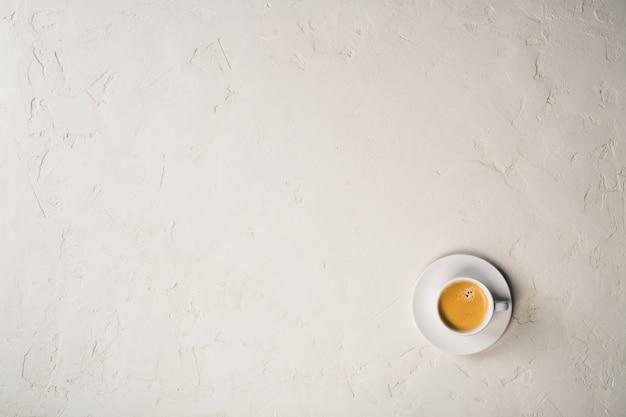 Tasse kaffee auf weißem zementhintergrund