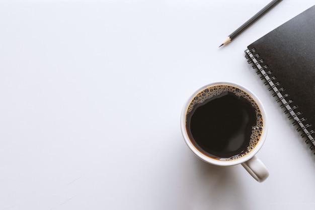 Tasse kaffee, bleistift und schwarzes notizbuch