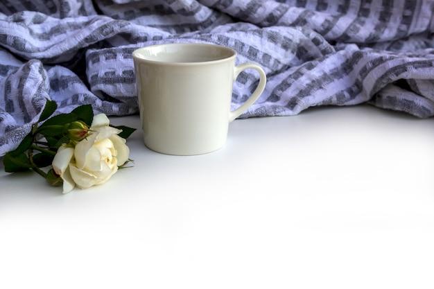 Tasse kaffee, blumen und plaid auf weißem schreibtisch.