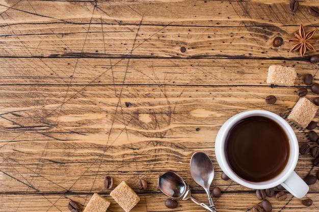 Tasse kaffee, brauner zucker und zimt mit anis auf holz.