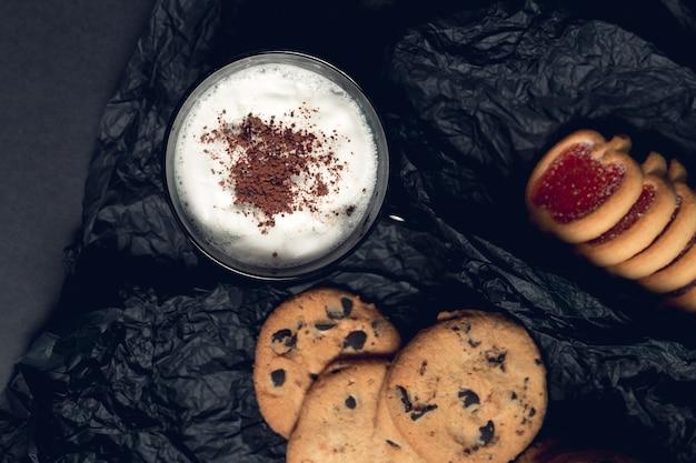 Tasse kaffee, cappuccino mit schokoladenplätzchen und keksen