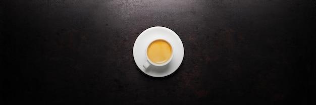 Tasse kaffee, der auf altem rustikalem hintergrund steht. banner-layout