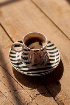 Tasse kaffee der hohen ansicht mit hölzernem hintergrund