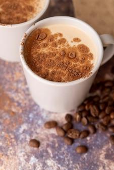 Tasse kaffee der hohen ansicht mit kakaopulver
