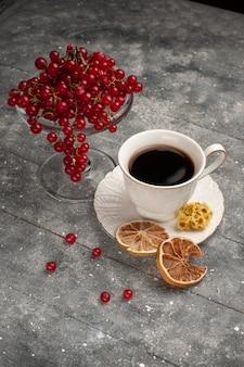 Tasse kaffee der vorderansicht mit frischen roten preiselbeeren auf der grauen kaffeekirschenfrucht des schreibtisches