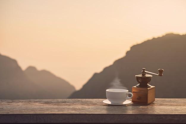 Tasse kaffee des heißen morgens mit gebirgshintergrund bei sonnenaufgang mit kopienraum