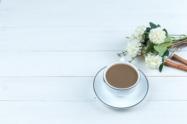 Tasse kaffee des hohen winkels mit blumen, zimt auf weißem holzbretthintergrund. horizontal