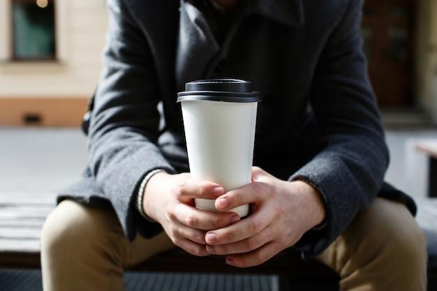 Tasse kaffee des weißen papiers, die in die arme des mannes geht