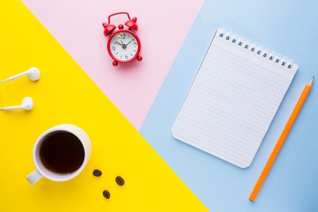 Tasse kaffee, ein wecker und ein notizbuch mit einem bleistift