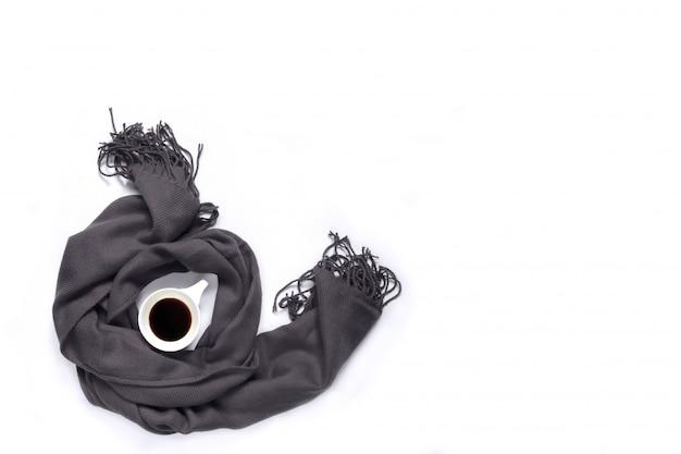 Tasse kaffee eingewickelt in einem grauen schal auf einem weißen hintergrund