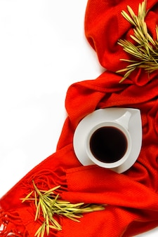 Tasse kaffee eingewickelt in einem orange schal auf einem weißen hintergrund