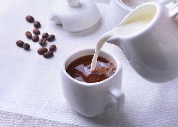 Tasse kaffee espresso, krug milch und schüssel mit zucker.