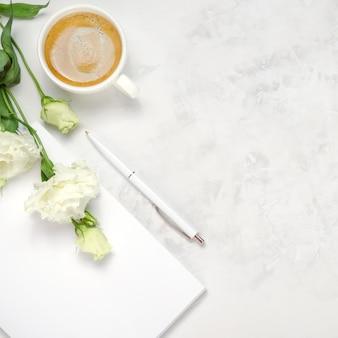 Tasse kaffee, eustoma, notizbuch und stift auf konkretem hintergrund. draufsicht