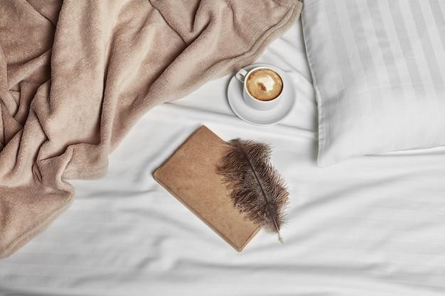 Tasse kaffee, feder und notizbuch auf dem bett
