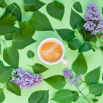 Tasse kaffee, flieder und grüne blätter auf einem grünen tisch. draufsicht