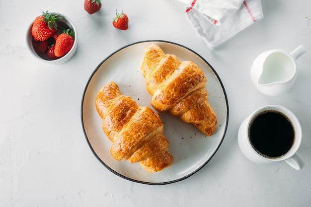 Tasse kaffee, frisch gebackene hörnchen und frische erdbeere auf hölzernem hintergrund