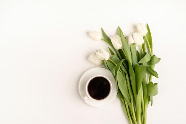Tasse kaffee, frisch geschnittene weiße tulpenblumen-draufsicht auf weißem hintergrund