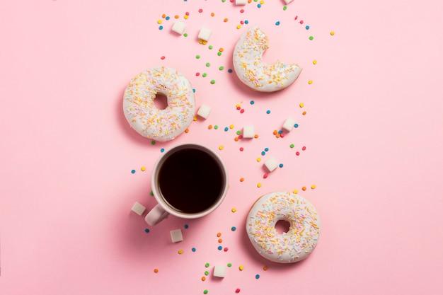 Tasse kaffee, frische leckere süße donuts auf einem rosa hintergrund. konzept von fast food, bäckerei, frühstück, süßigkeiten. minimalismus. flache lage, draufsicht, kopierraum.
