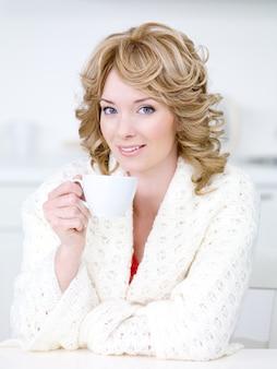 Tasse kaffee für junge schöne blonde frau, die in der küche sitzt