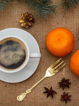 Tasse kaffee, gabel, orangen, sternanis und zimt mit fichtenzweig auf sackleinen. ansicht von oben.