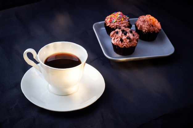 Tasse kaffee gedient mit schokoladenkleiner kuchen. süßspeise mit lieblingsgetränk.