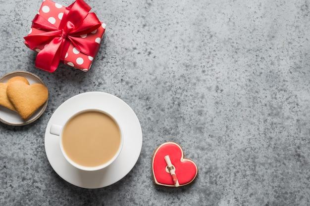 Tasse kaffee, geschenk und kekse in form des herzens mit liebesbrief auf rosa hintergrund. valentinskarte. flache lage, draufsicht, kopierraum.